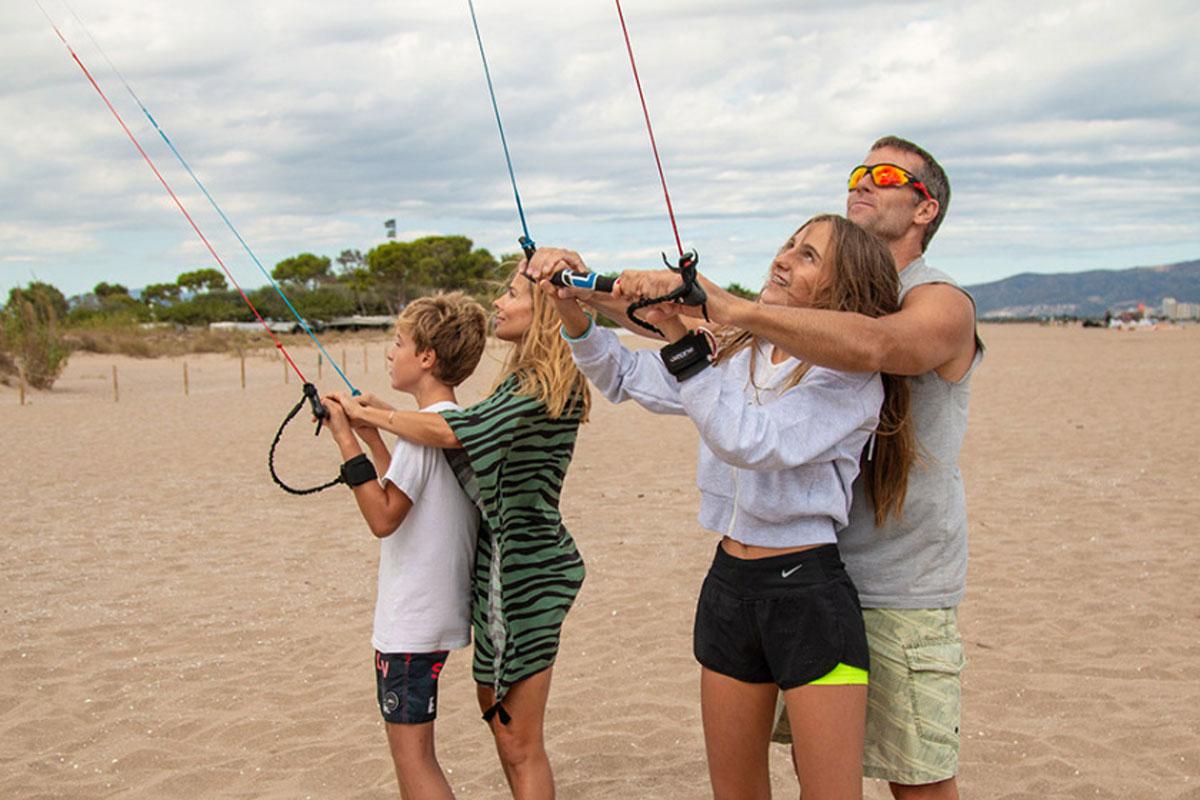 Rodzina steruje latawcem treningowym do kitesurfingu.
